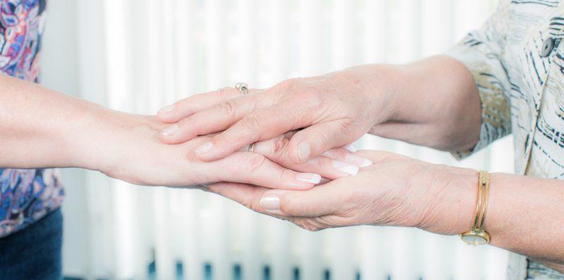 Zwei Personen reichen einander beruhigend die Hände.
