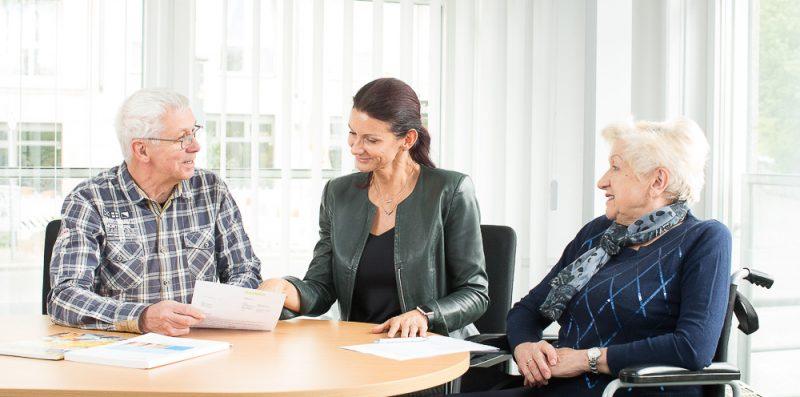 Eine Frau im Rollstuhl und ein Mann werden von einer Mitarbeiterin der Pflegestützpunkte beraten.