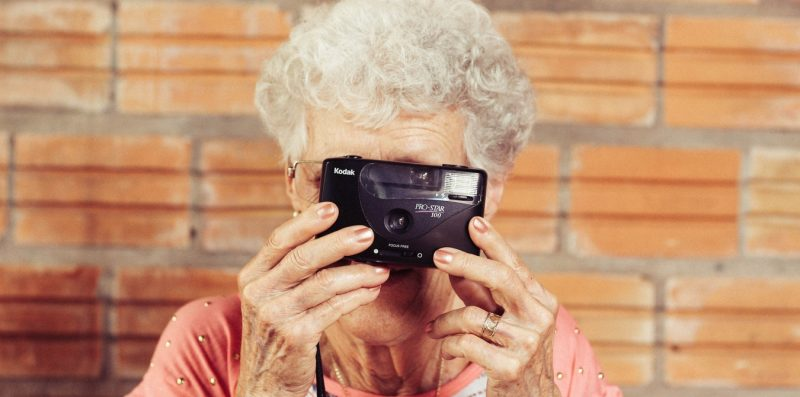 Elderly woman takes picture with a camera.
