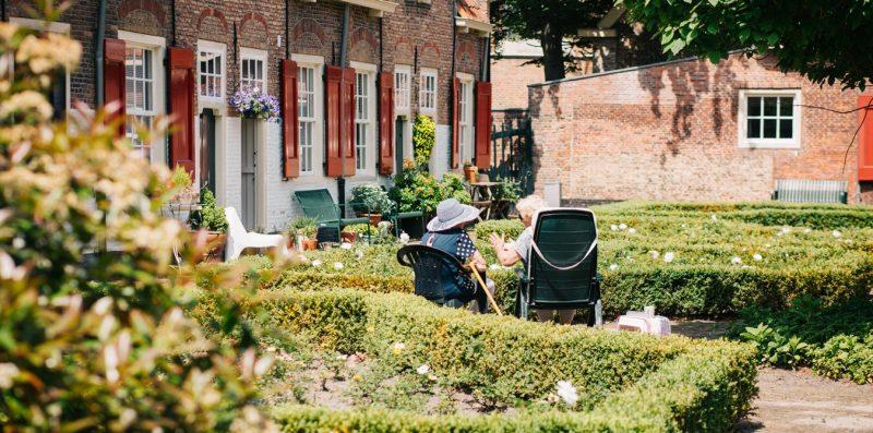 İki kadın bir evin bahçesinde gün ışığında oturmaktadır.