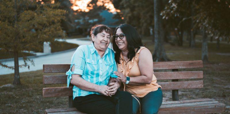 Zwei Frauen, die auf einer Bank sitzen und miteinander lachen.