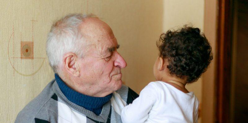 Älterer Mann mit Pflegebedarf und Kind auf dem Arm