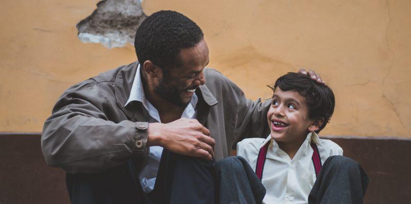 Ein Junge und ein Mann lachen sich an.