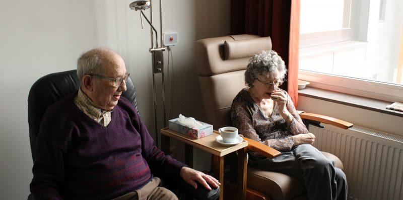Eine ältere Dame und ein älterer Herr sitzen zusammen